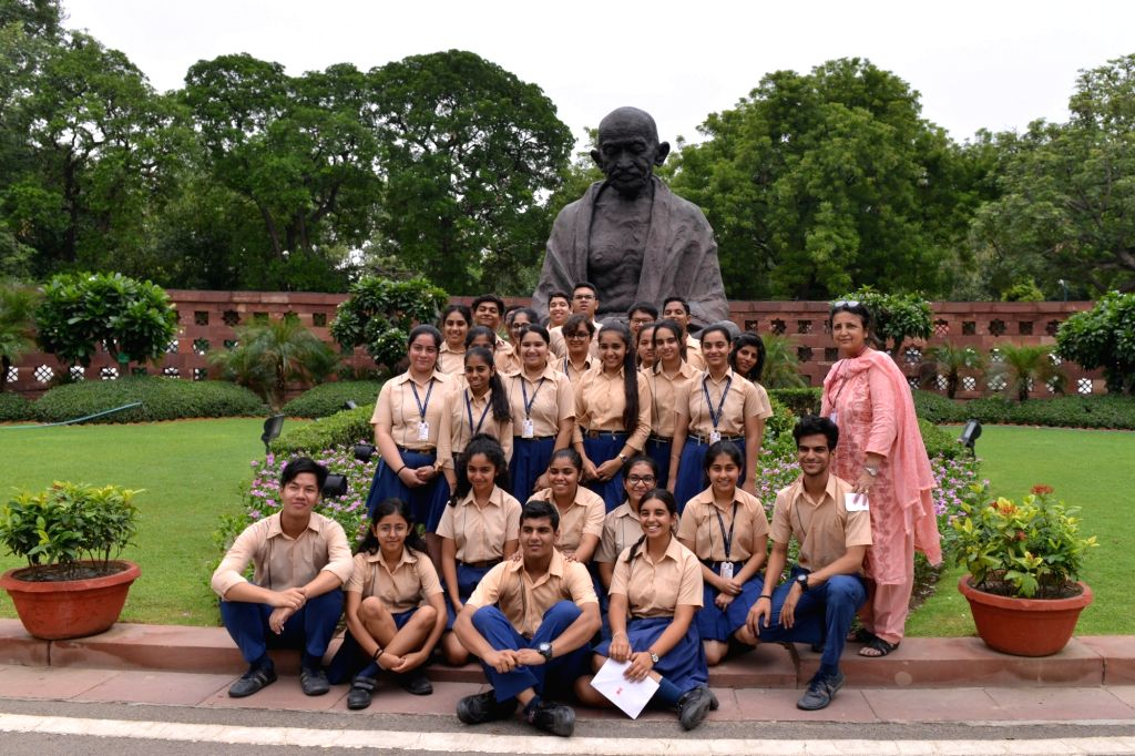 School students pose for a group photograph in front of the Gandhi statue at Parliament, in New Delhi on July 16, 2019.