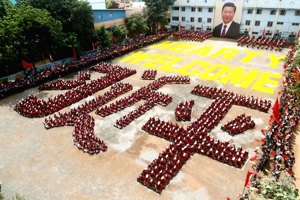 School students sit in the human formation of the name of Chinese President Xi Jinping in Chinese language during a programme organised to welcome the Chinese President ahead of his arrival ... - Narendra Modi