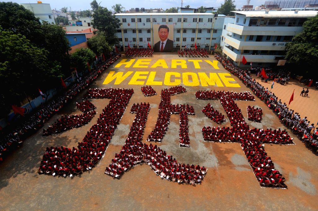 School students sit in the human formation of the name of Chinese President Xi Jinping in Chinese language during a programme organised to welcome the Chinese President ahead of his ... - Narendra Modi