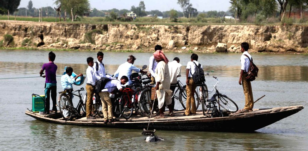 School students use a boat to cross the Gomti river after removal of a temporary bridge near Gaughat of Lucknow on Aug 27, 2014.