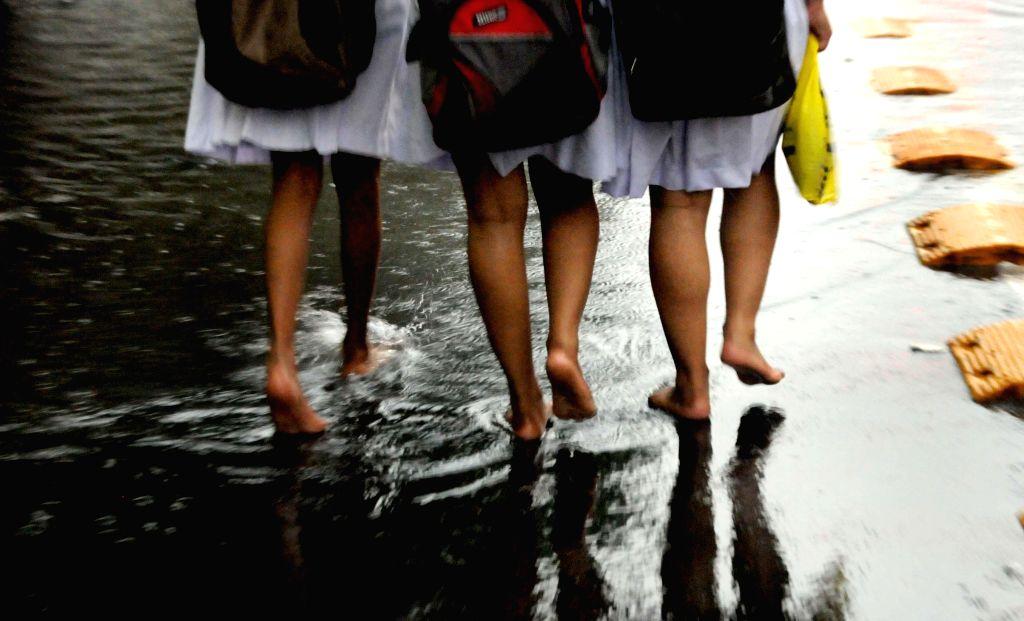 School students walk bare foot after rains in Kolkata on July 2, 2014.