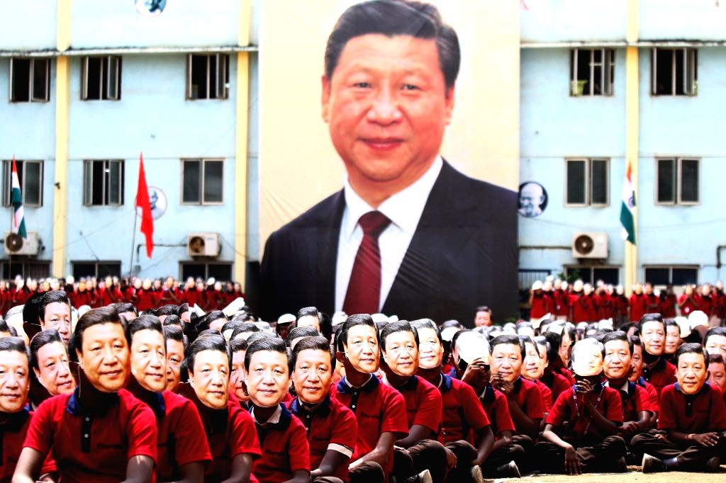 School students wearing the masks of Chinese President Xi Jinping sit in the human formation of the name of the Chinese President during a programme organised to welcome him ahead of his ... - Narendra Modi