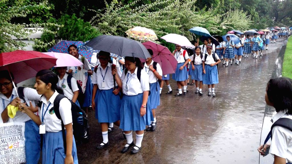 Schools girls use umbrellas to protect themselves from rains in Patna on July 18, 2016.