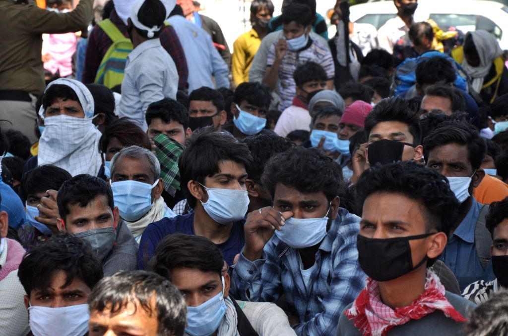 Scores of migrant workers heading back home seen at Anand Vihar bus terminal close to Delhi's border with Ghaziabad on Day 5 of the 21-day countrywide lockdown imposed to contain the ...