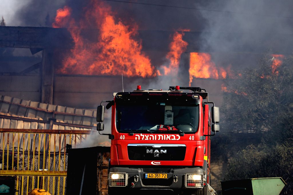 SDEROT, Nov. 12, 2019 - Israeli firefighters put out fire at a burning factory hit by rockets fired from the Gaza Strip in the southern Israeli town of Sderot, Nov. 12, 2019. Some 50 rockets were ...