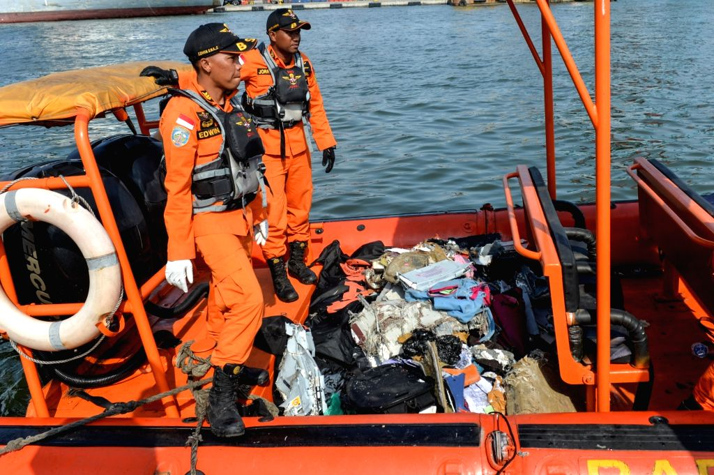 :Search and Rescue officers stand on the speed boat carrying debris of passenger jet and body of victims at the Tanjung Priok port, Jakarta, Indonesia, Oct. 29, ...