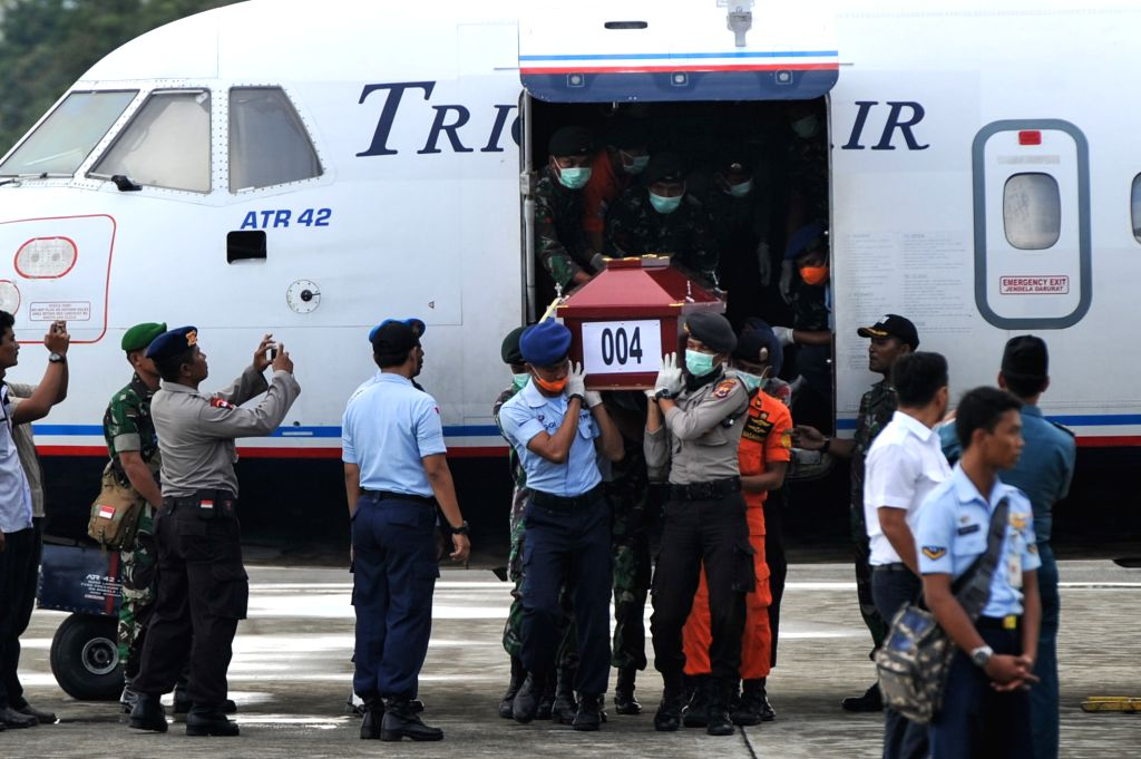 Search and Rescue (SAR) personnels, policemen and the Indonesian National Armed Forces (TNI) carry a coffin that contains the body of a victim from the crashed ATR ...