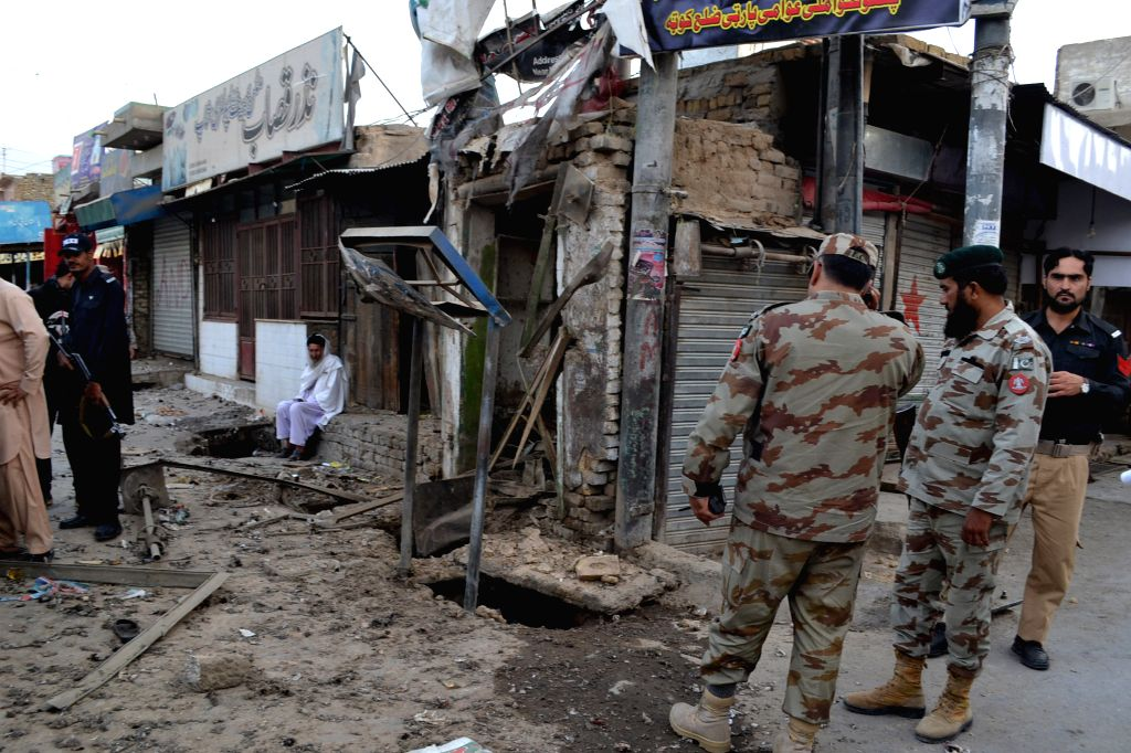 Security officials examine the blast site in southwest Pakistan's Quetta, Aug. 11, 2015. At least two policemen were killed and six other people were injured in a ...