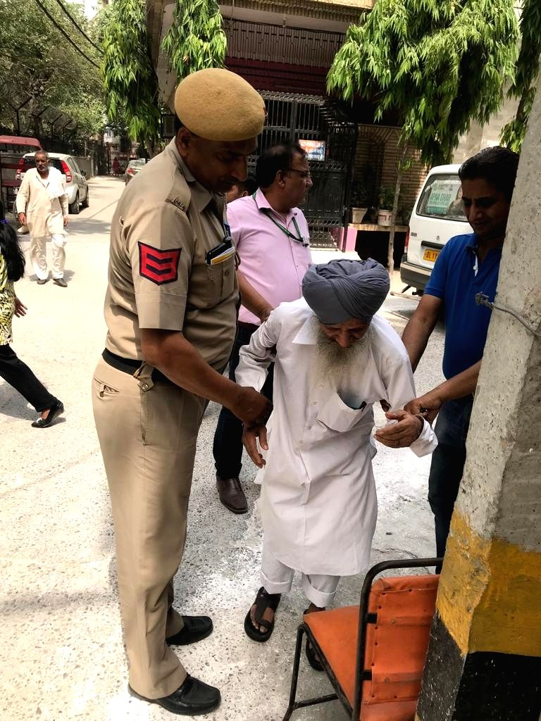 Security personnel assist an elderly man who arrived to cast his vote during the sixth phase of 2019 Lok Sabha elections, in Delhi's Prashant Vihar on May 12, 2019.