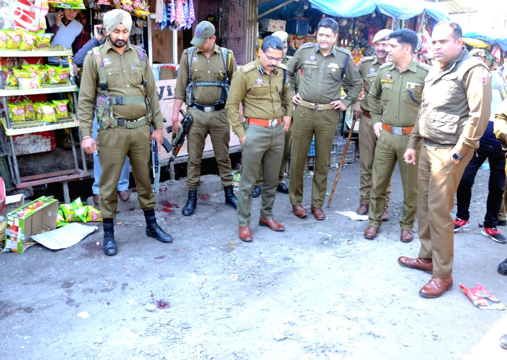 Security personnel carry out investigation at the site, where a blast took place after a grenade attack by militants at the busy main bus terminus in Jammu and Kashmir, on March 7, 2019. ...