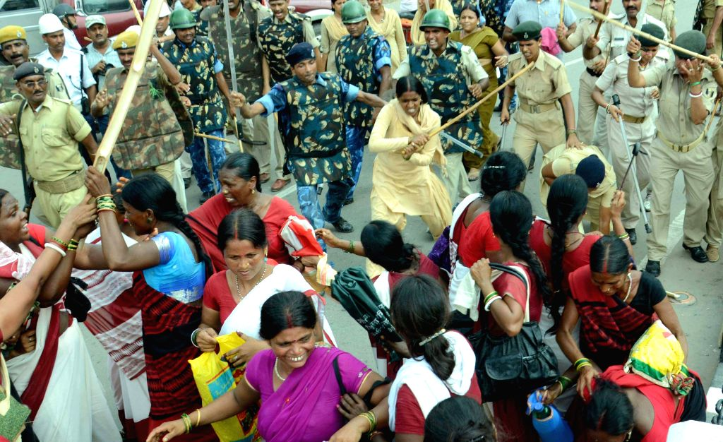 Security personnel charge batons on Anganwadi workers in Patna on August 10, 2015.