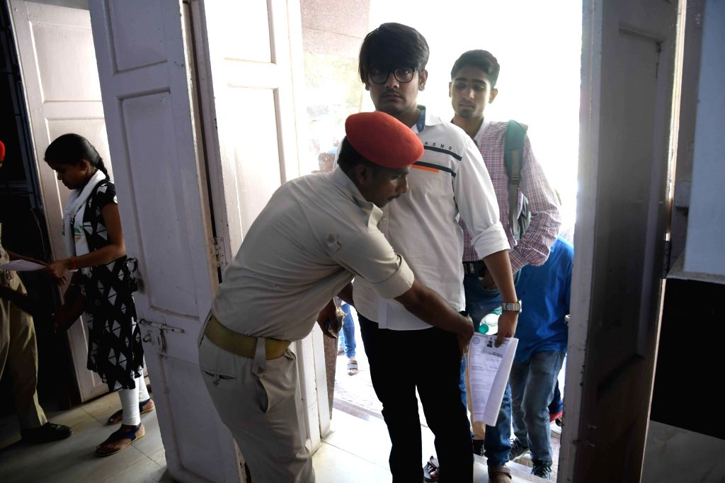 Security personnel check students before entering the examination hall as they appear for Common Law Admission Test (CLAT) exams 2019, in Patna on May 26, 2019.