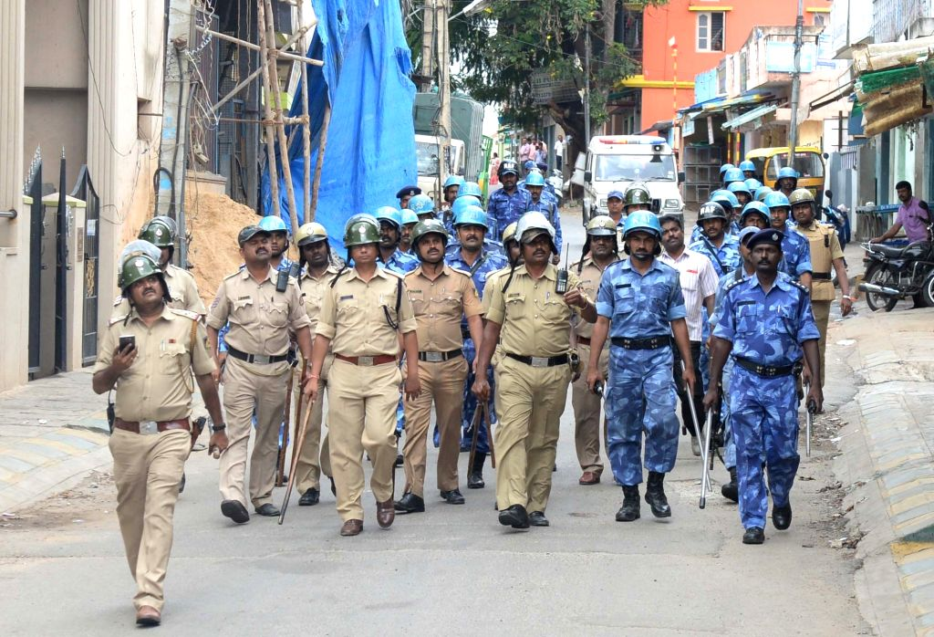 Security personnel conduct flag march on Bengaluru roads on Sept 13, 2016. An uneasy calm prevailed in the city where one person was killed in police firing on Monday night and curfew is ...