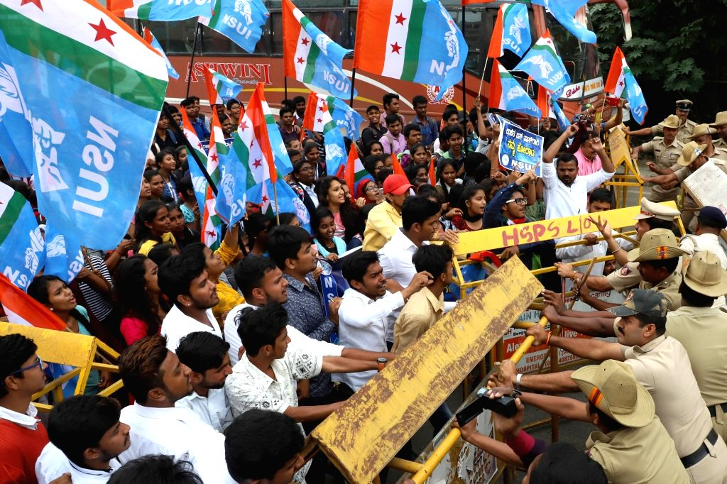 Security personnel detains National Students Union of India (NSUI) activists stage a demonstration to press for free bus passes for students at Anand Rao Circle, in Bengaluru, on July 19, ... - Anand Rao Circle