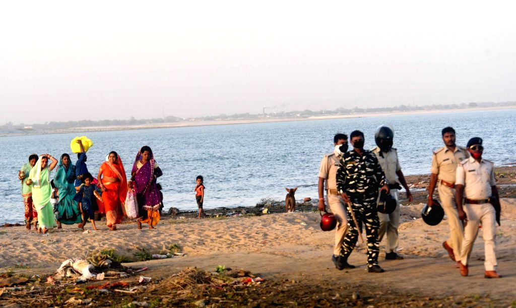 Security personnel keep a vigil as a beeline of devotees head towards the banks of Ganga river to perform rituals during Chaiti Chhath celebrations amid countrywide lockdown imposed to contain ...