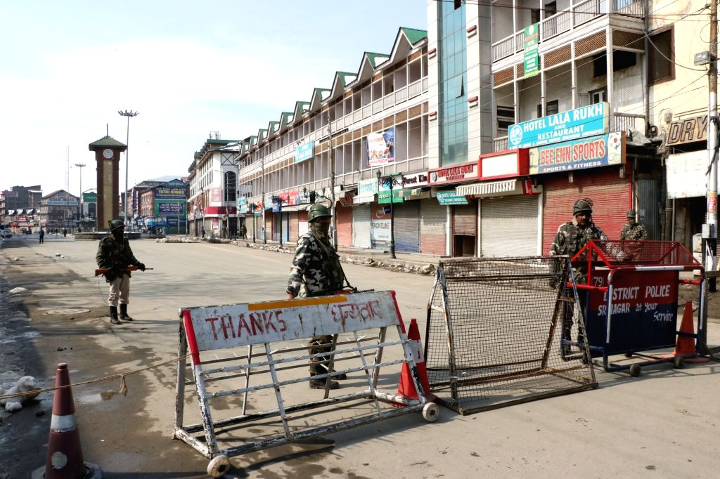 Security personnel man a Srinagar street during a separatist-called shutdown in the Kashmir Valley to mark the 35th death anniversary of Jammu and Kashmir Liberation Front (JKLF) founder, ...