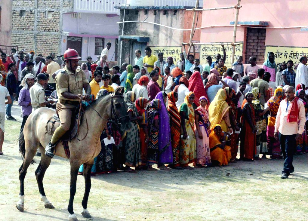 Security personnel mounted on horses stand guard as voters queue up to cast their votes for the fourth phase of 2019 Lok Sabha elections, in Bihar's Munger on April 29, 2019.
