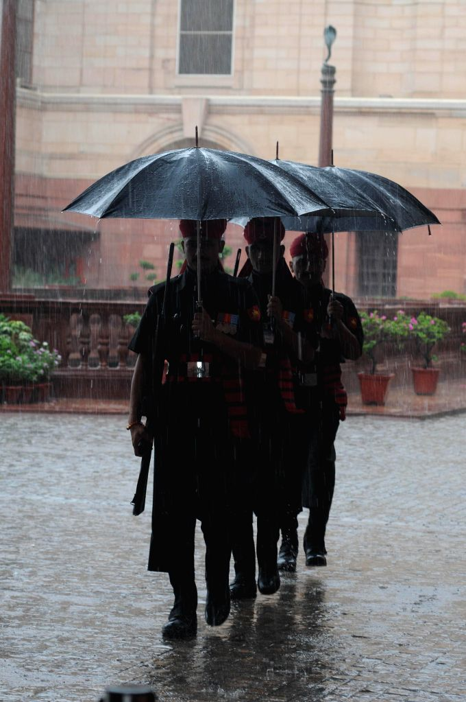 Security personnel perform their duties despite heavy rains in New Delhi on Aug 10, 2014.
