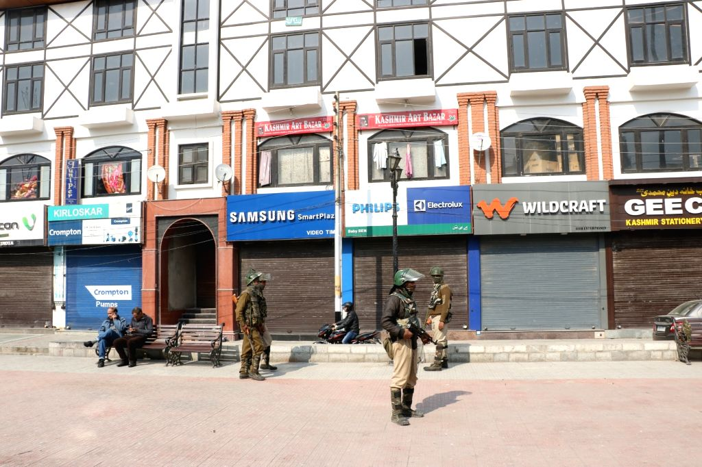 Security personnel stand guard and shops remain closed during a shutdown called by separatists to protest against the killings of two Kashmiri militants; in Srinagar on Oct 25, 2018.