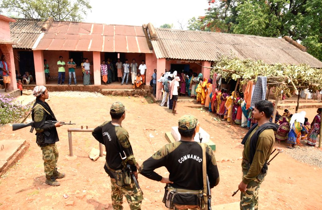 Security personnel stand guard as people vote for the second phase of 2019 Lok Sabha elections, at a polling booth at Sadingia in Odisha's Kandhamal, on April 18, 2019.