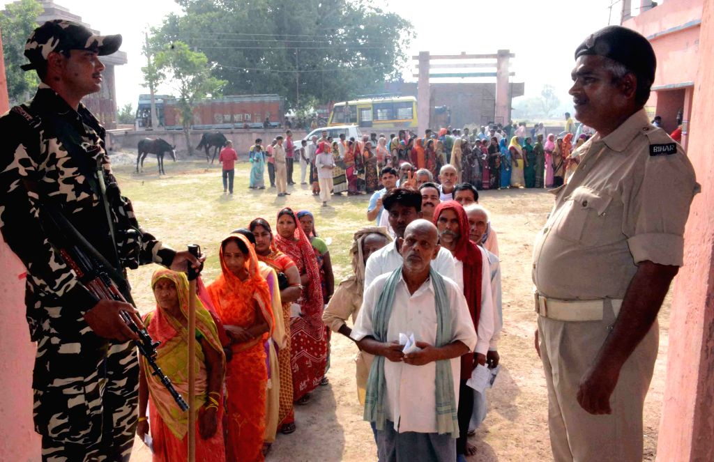 Security personnel stand guard as voters queue up to cast their votes for the fourth phase of 2019 Lok Sabha elections, in Bihar's Munger on April 29, 2019.