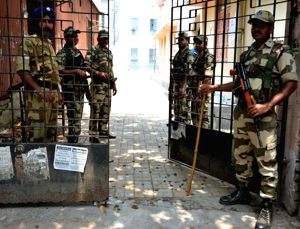 Security personnel stand guard at the polling station number 200 of Kolkata's Uttar parliamentary constituency during re-polling after the Election Commission of India (ECI) declared void ...