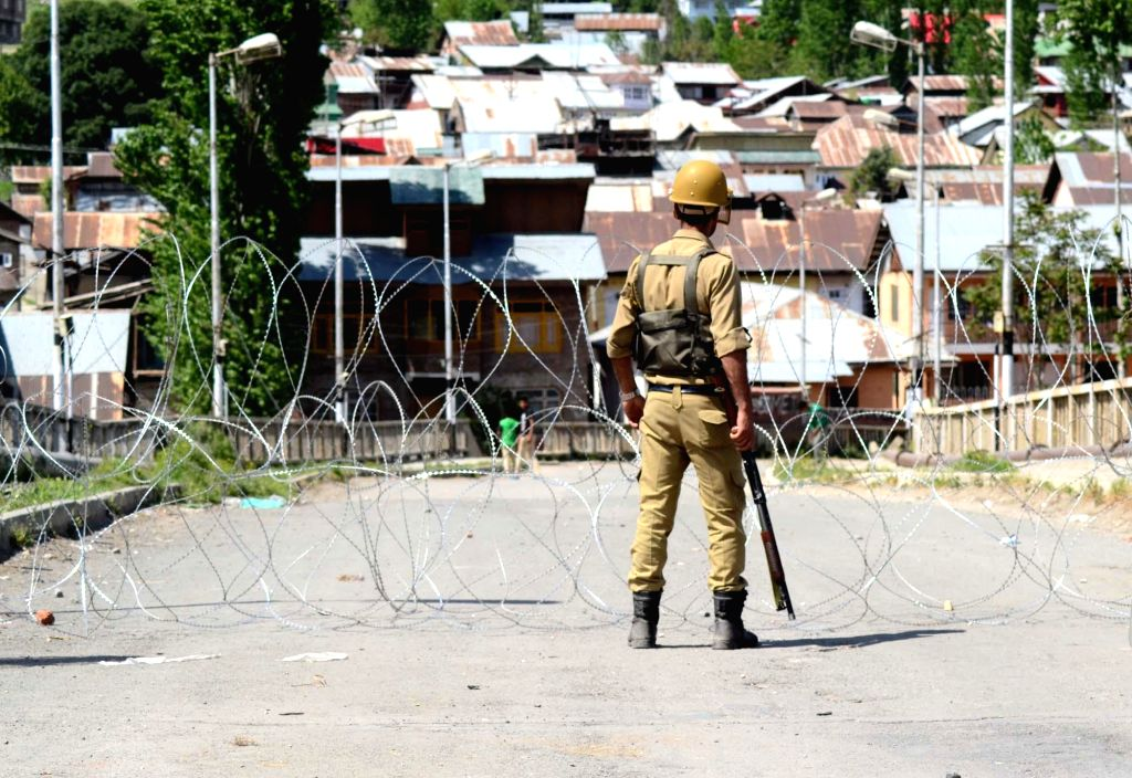 Security personnel stand guard in Baramulla as general strike continues in Baramulla for last three days against detention of youths by state police before polling in North Kashmir on May 10, 2014.