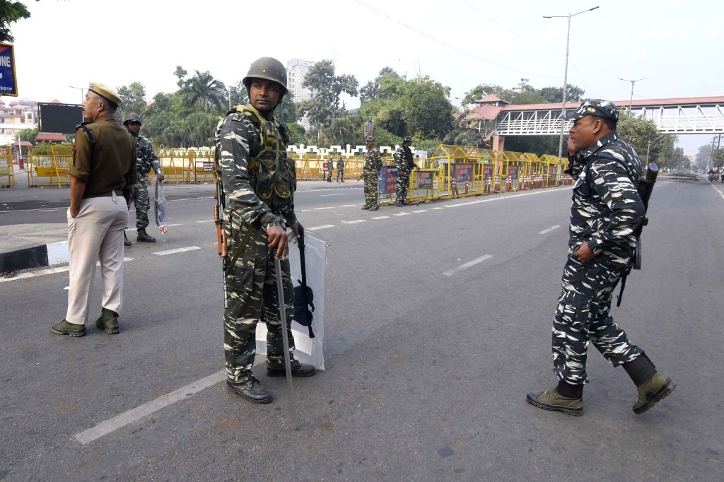 Security personnel stand guard near Janta Bhawan during an indefinite curfew clamped by the Assam government following deteriorating law and order situation over the Citizenship (Amendment) ...