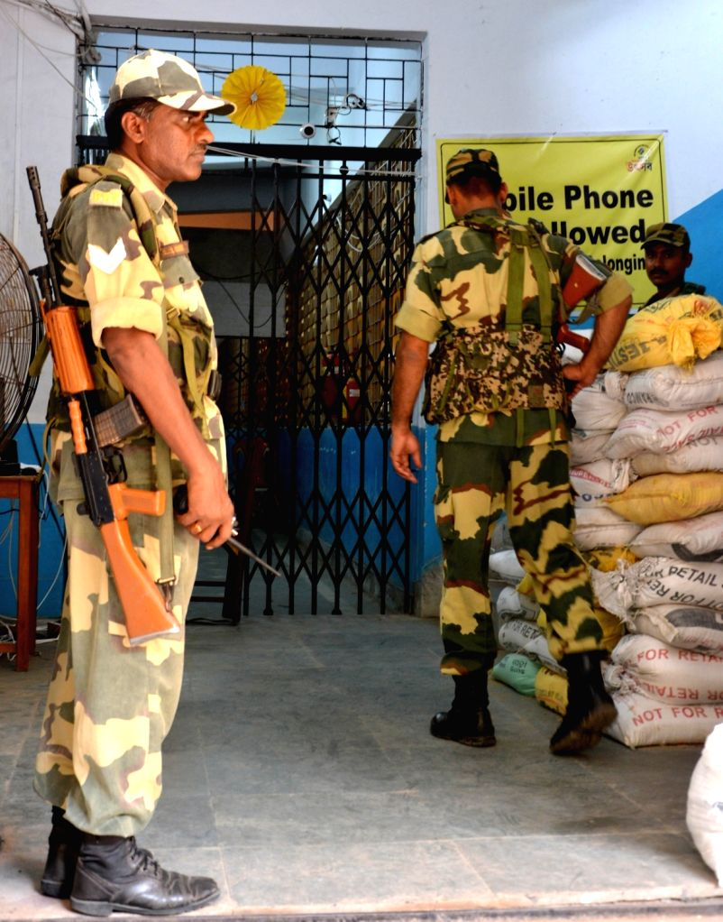 Security personnel stand guard outside a strong room where Electronic Voting Machines (EVM) have been stored after the last phase of 2019 Lok Sabha elections concluded on Sunday, in Kolkata ...