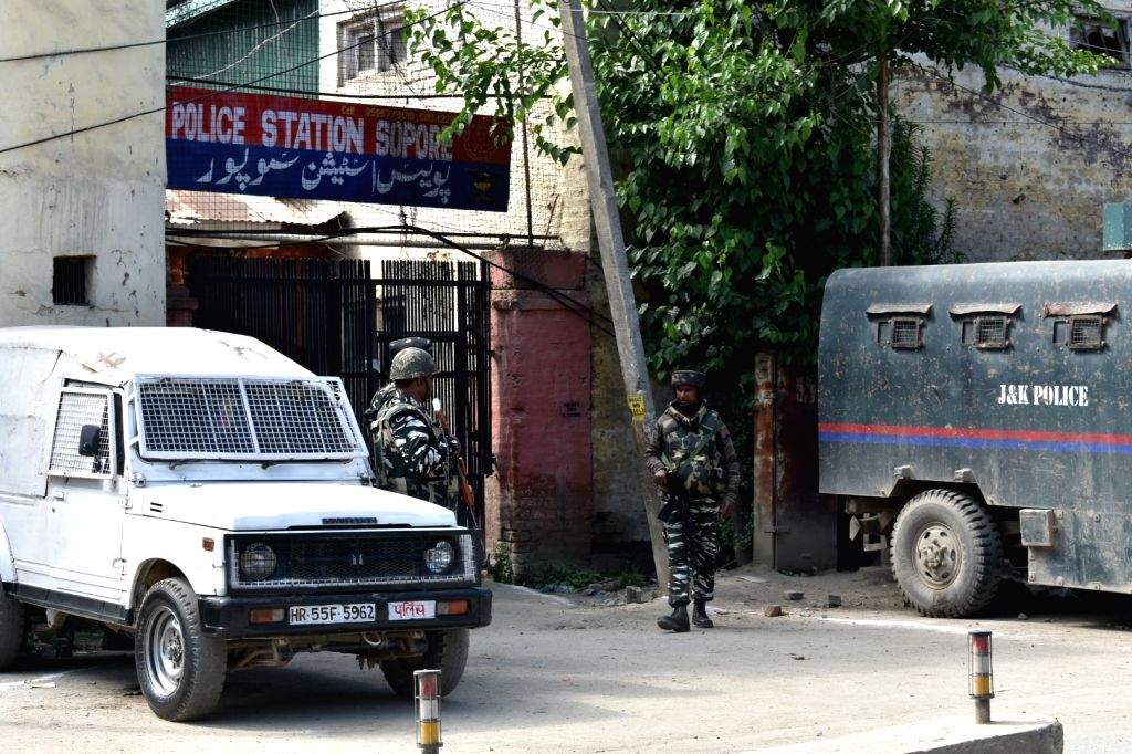 Security personnel stand guard outside the police station where militants hurled a grenade, injuring two policemen, in Jammu and Kashmir's Sopore on June 7, 2019.