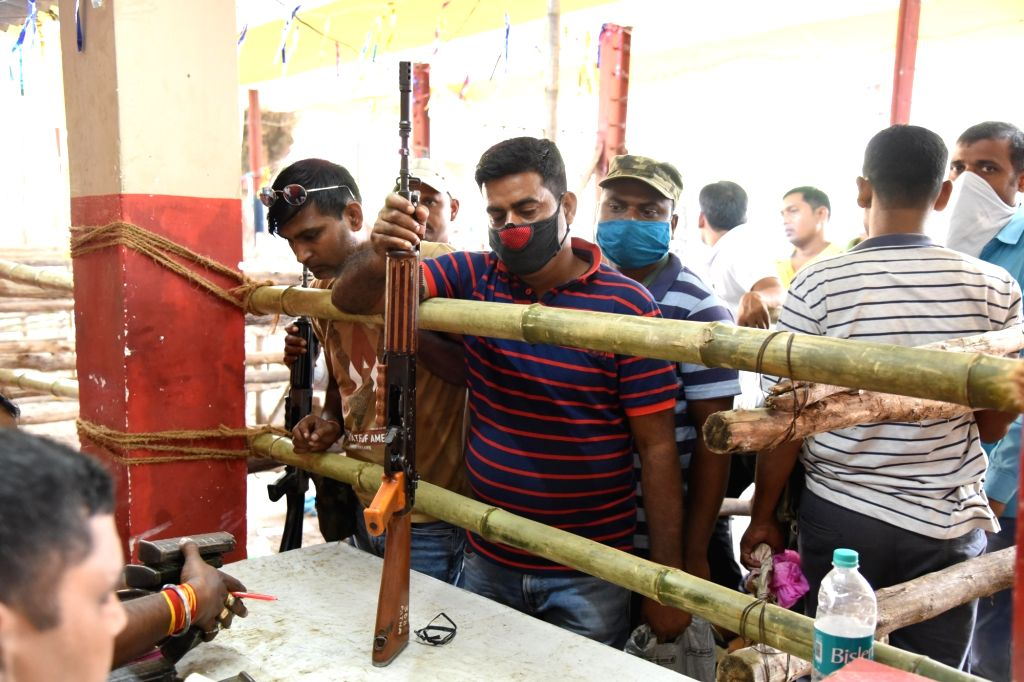 Security personnel standing in a queue to receive weapons for election duty in forthcoming Bihar Assembly polls, in Patna on Sunday October 25,2020.