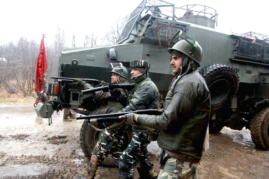 Security personnel take position during a gunfight with militants in Heff Shermal village of Jammu and Kashmir's Shopian district, on Jan 22, 2019. Two militants were killed in the gunfight.