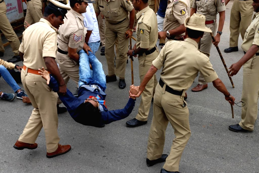 Security personnel takes away National Students Union of India (NSUI) activists as they stage a protest to press for free bus passes for students at Anand Rao Circle, in Bengaluru, on July ... - Anand Rao Circle