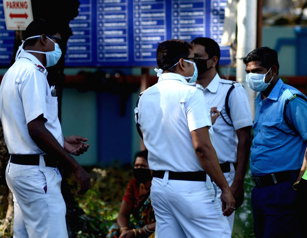 Security personnel wear masks as a precautionary measure against COVID-19 amid coronavirus pandemic, outside the Beleghata ID hospital in Kolkata on March 20, 2020.