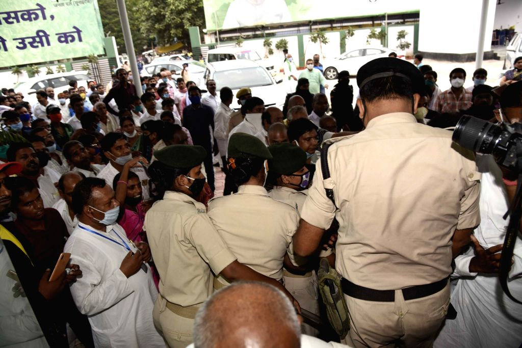 Security personnel with JD-U workers during protest against seat distribution at party office ahead of Bihar Assembly elections, in Patna on Oct 7, 2020.
