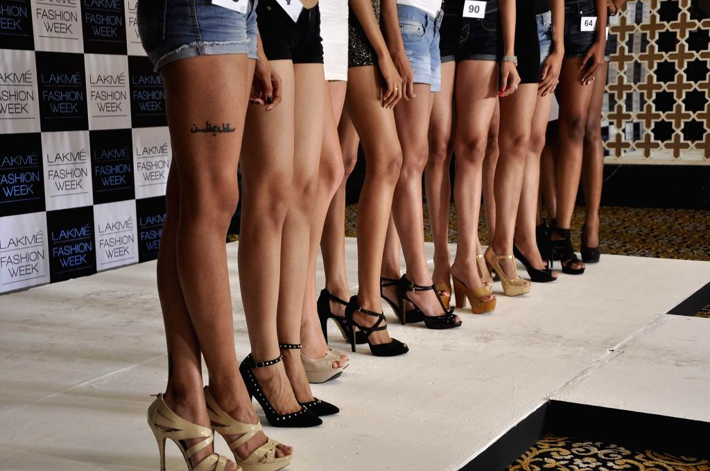 Selected models pose with Models await their turn to audition for the Lakme Fashion Week, in Mumbai on July 3, 2014. The LFW Winter/Festive which is scheduled for August 22-24, 2014.