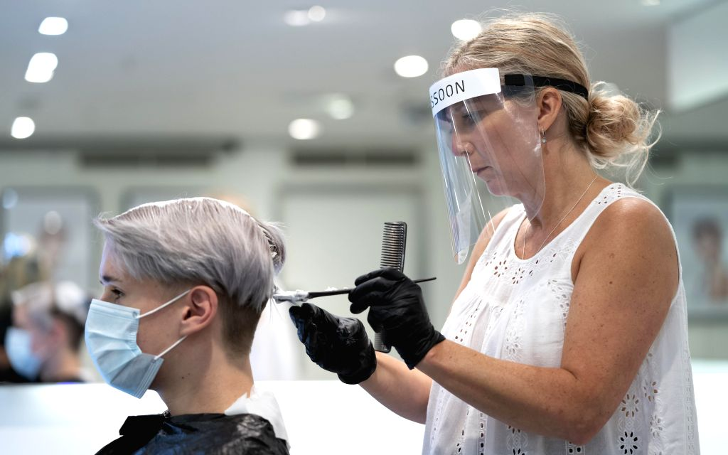 Senior colour director Chloe Thompson (R) wearing personal protective equipment practices hair bleaching on her colleague Nathan Tanner for the reopening of ... - Chloe Thompson