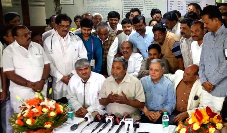 Senior Congress leader Siddaramaiah accompanied by doctors talks to press after being discharged from the hospital in Bengaluru on Dec 15, 2019.