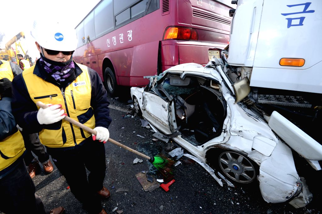 A firefighter works at the site of a car pileup accident in Seoul, Feb. 11, 2015. At least two people have been confirmed dead, with 65 others including seven Chinese