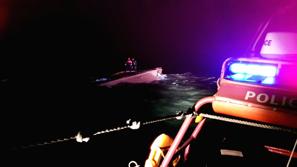 SEOUL, Jan. 21, 2018 - South Korean coast guards reach the cpasized fishing boat near South Korea's western waters, Jan. 21, 2018. Three people were found dead as a suspected Chinese fishing boat ...