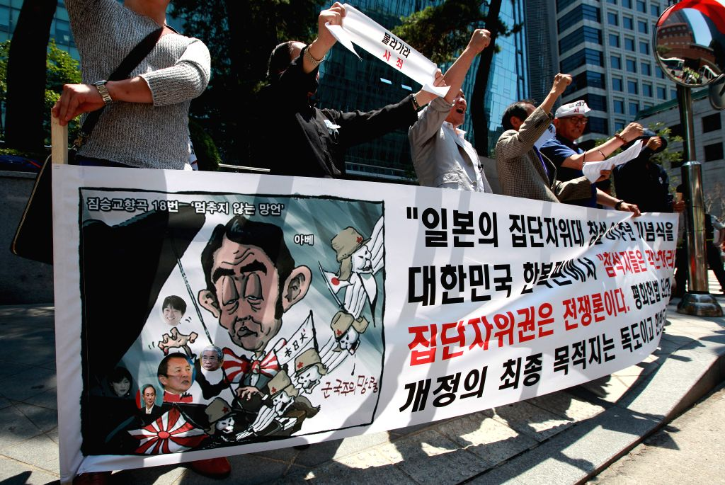 Protesters hold a banner during a rally against Japan's right to collective self-defense in front of the Japanese Embassy in Seoul, South Korea, July 11, 2014.
