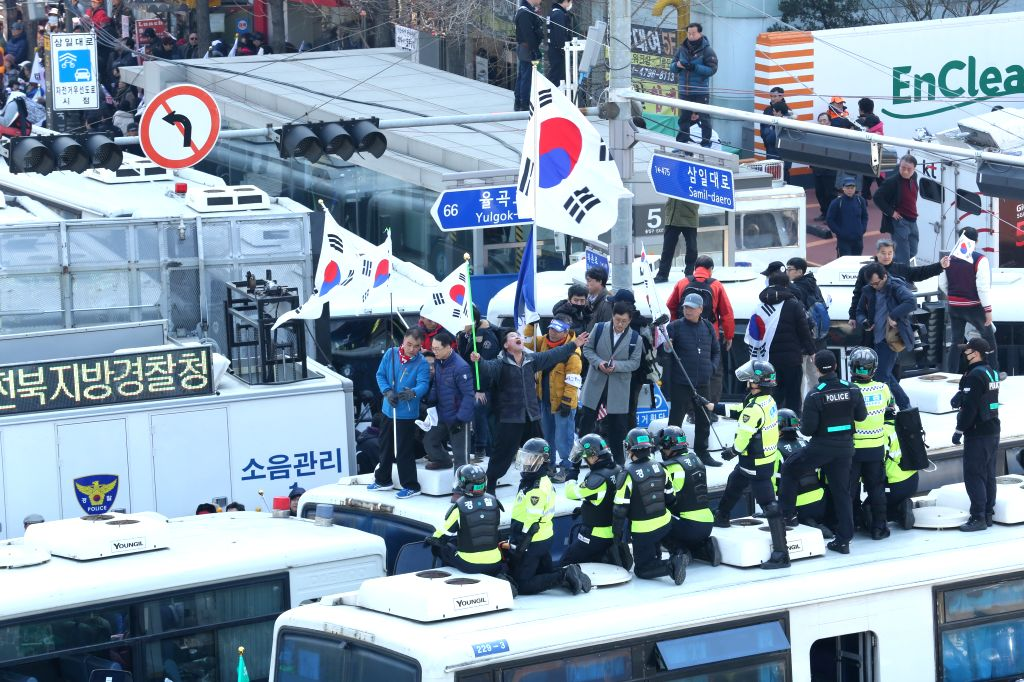 SEOUL, March 10, 2017 - Park Geun-hye's supporters stand on a police vehicle during a rally in Seoul, South Korea, March 10, 2017. Two of South Korean participants in a pro-Park Geun-hye rally held ...