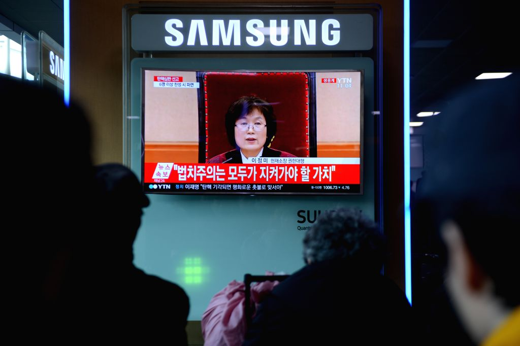 SEOUL, March 10, 2017 - People watch a TV screen broadcasting news about Park Geun-hye's impeachment in Seoul, South Korea, March 10, 2017. South Korean President Park Geun-hye was permanently ...