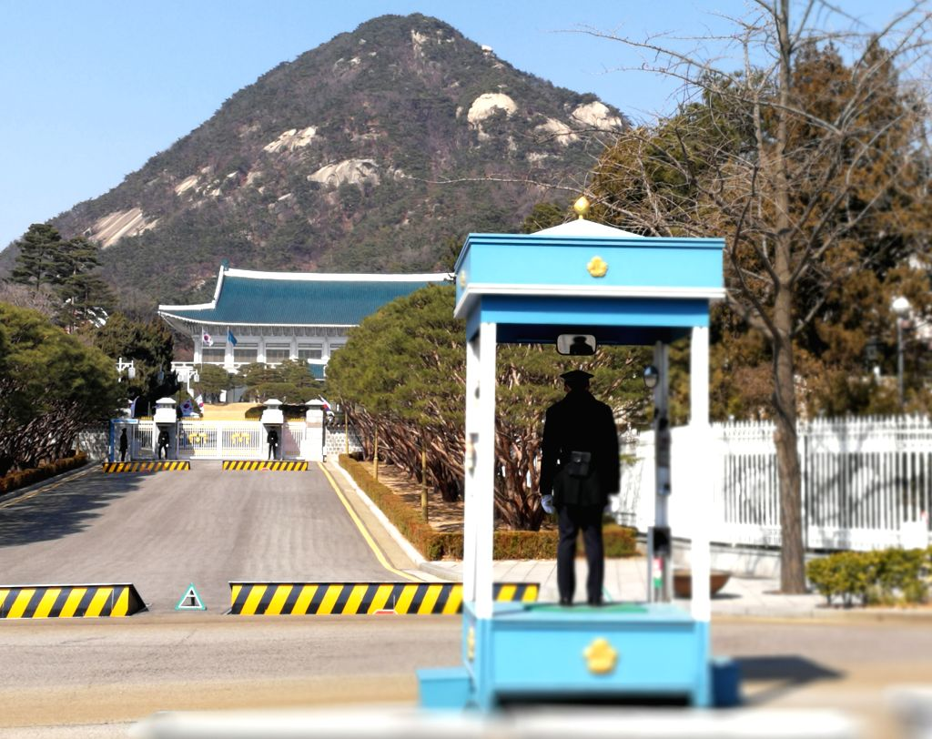 SEOUL, March 10, 2017 - Photo taken by mobile phone shows police stand guard outside the presidential Blue House in Seoul, South Korea, March 10, 2017. South Korean President Park Geun-hye was ousted ...