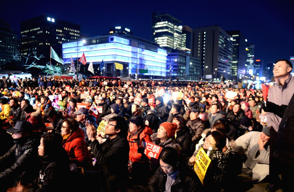 SEOUL, March 10, 2017 - South Korean demonstrators hold banners during a candle-lit rally in Seoul on March 10, 2017. South Korean President Park Geun-hye was ousted as the country's head of state on ...