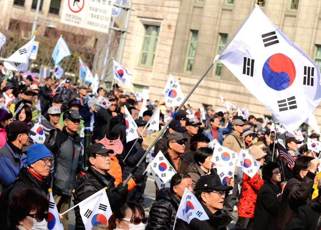 SEOUL, March 11, 2017 - Supporters of South Korea's ousted leader Park Geun-hye wave flags during a rally in Seoul, South Korea, March 11, 2017.