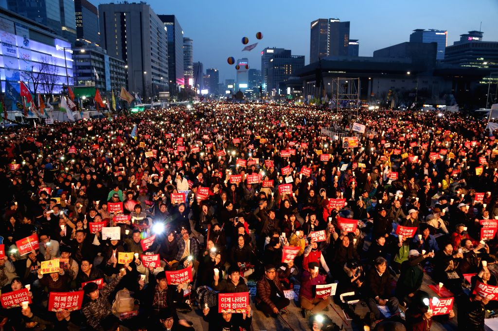 SEOUL, March 12, 2017 - Demonstrators against South Korea's ousted leader Park Geun-hye attend the last candlelight rally at Gwanghwamun Square in Seoul, South Korea, March 11, 2017. Hundreds of ...