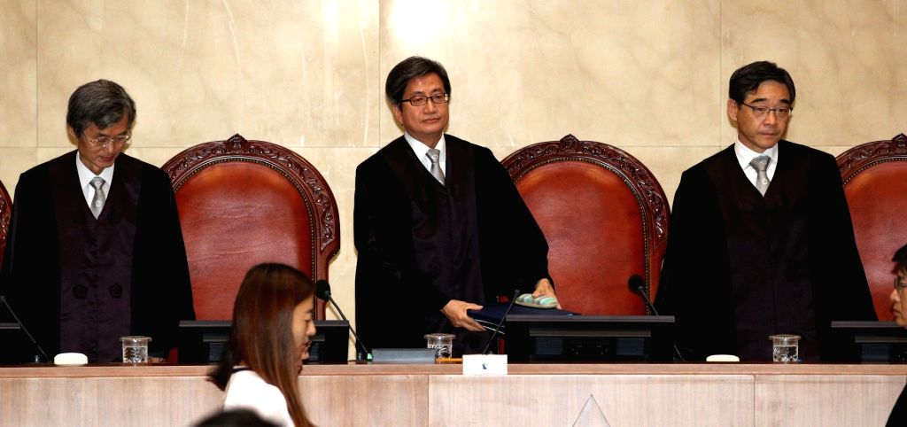 Seoul: Supreme Court Chief Justice Kim Myeong-su (C) and other justices take their seats at a verdict hearing at the court in Seoul on Aug. 29, 2019, over a string of allegations, including bribery and abuse of power, that involve former President Pa