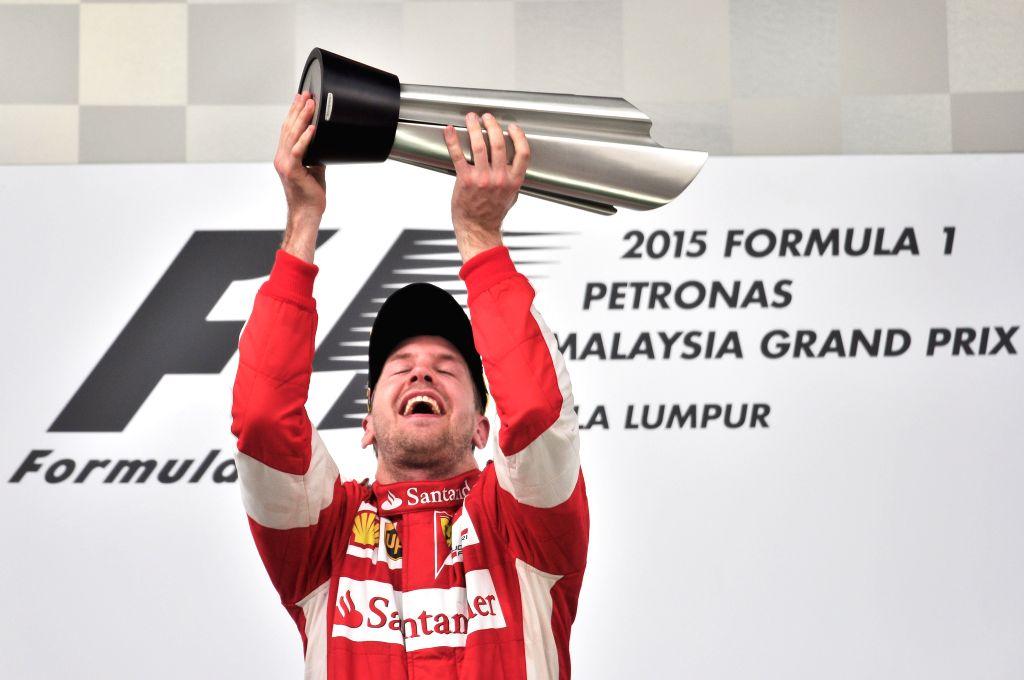 Ferrari driver Sebastian Vettel of Germany celebrates on the podium after winning the Malaysian Formula One Grand Prix in Sepang, Malaysia, March 29, 2015. ...