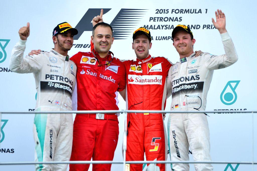 Ferrari driver Sebastian Vettel (2nd R) of Germany poses with Mercedes driver Nico Rosberg (1st R) of Germany, Mercedes driver Lewis Hamilton (L) of Britain and ...